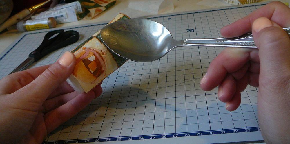 Прижмите салфетку к свече и осторожно проводите горячей ложкой